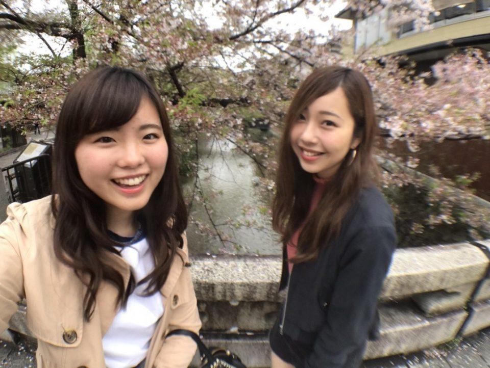 桜をバックに写真を撮る女子大生