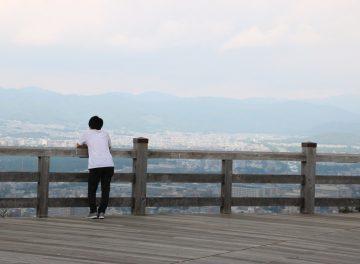 景色を眺める大学生